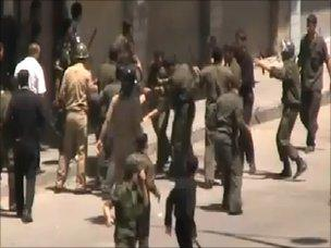 Amateur video purportedly showing men in civilian clothes joining soldiers and police to beat and detain protesters in Homs (June 2011)