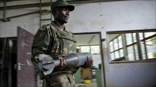 Ugandan soldier serving with the African Union Mission in Somalia carries a shell that were used by al-Shabab to make improvised explosive devices - August 2011