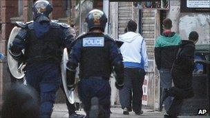 Riot police chase youths during civil disturbances in Manchester