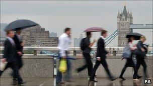 City workers walk over London Bridge in central London