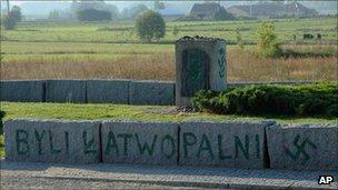 """An inscription reading """"They were flammable"""" and a Nazi swastika are seen on the Jewish war memorial in Jedwabne, Poland"""