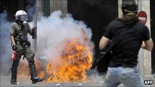 A protester faces a riot policeman in front of the Greek Parliament on 29 June 2011 in Athens