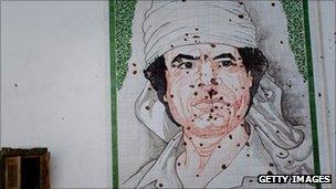 Bullet-ridden mosaic of Col Gaddafi on a wall in Tripoli on 29 August 2011