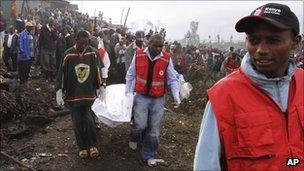 Kenya Red Cross personnel carry the lifeless body of a victim of a gasoline pipeline explosion in a slum area of Nairobi, Kenya, Tuesday, Sept. 13