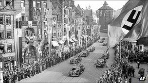 Adolf Hitler salutes supporters from a car as he passes through Nuremberg, 5 September 1938