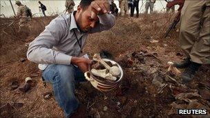 A man collects bones at the site of Abu Salim prison in Tripoli, 25 September 2011
