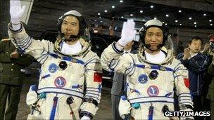Chinese astronauts Fei Junlong (L) and Nie Haisheng wave before boarding the Shenzhou VI spacecraft at Jiuquan Satellite Launch Center on 12 October 2005 in Jiuquan, Gansu province, northwest China