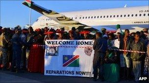 A crowd holds a banner at sunrise at the international airport in Windhoek on Tuesday, as Germany returns the skulls taken for experiments more than a century ago
