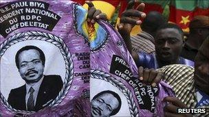 """People hold a piece of cloth with pictures of Cameroon""""s President Paul Biya, near a street stall at the Carrefour Wada district in the capital Yaounde October 7, 2011."""