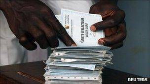 """A man searches for his voting card at a polling unit during the presidential election in Cameroon""""s capital Yaounde October 9, 2011."""