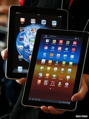 A shop employee holds an Apple iPad behind a Samsung Galaxy Tab