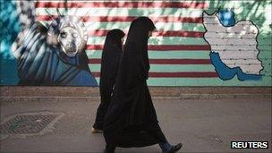 Two women in front of an anti-American mural in Tehran