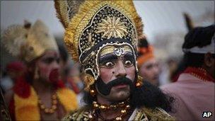 An Indian Hindu man dressed as demon king Ravana looks on at a venue of Dussehra festivities