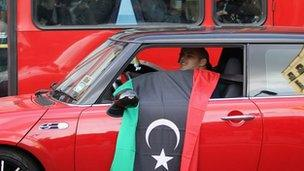 A man waves a Libyan flag from his car near the Libyan embassy in Knightsbridge on October 20, 2011