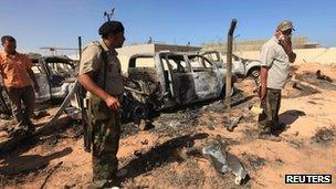 Anti-Gaddafi fighters stand in front of damaged cars, October 21, 2011, after an attack by Nato on a convoy of Gaddafi loyalists in Sirte
