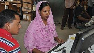 A Bangladeshi woman is given help on a computer