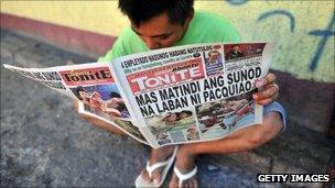 Man reads a paper on a Manilla street