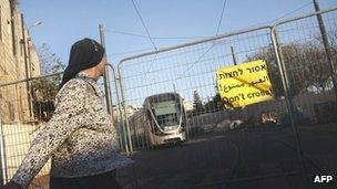 An ultra orthodox Jewish woman stands by an unfinished section of the railway in Jerusalem, November 16, 2010