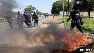 Liberian riot police walk past a burning tyre during clashes with supporters of presidential challenger Winston Tubman in Monrovia November 7, 2011.