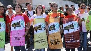 """Protesters wearing banners saying """"Young people against violence"""""""