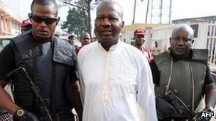 Baba Suwe escorted by armed guards (4 November 2011)