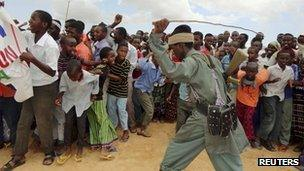 A member of al-Shabab controls residents as they participate in a demonstration against Kenya's incursion inside Somalia in Elasha, outside Mogadishu, on October 2011