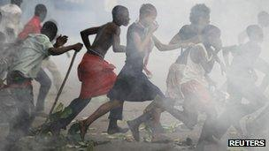 Opposition UDPS supporters run through a cloud of tear gas outside N'Djili airport in Kinshasa