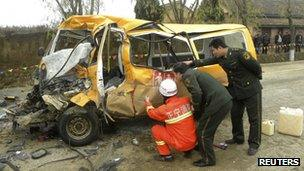 Rescuers inspect a school bus after it collided with a truck at a traffic accident site in Yulinzi township of Zhengning county, Gansu province, 16 November 2011
