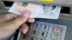 Generic pic of a person withdrawing cash from ATM