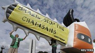 Greenpeace activists holds an inflatable balloon, shaped like a chainsaw to protest the vote on the new Forest Code in Brasilia December 6, 2011