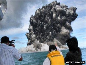 People watch as smoke billows up from an underwater volcano