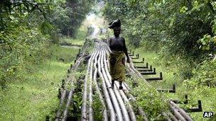 Woman walks on oil pipeline in Warri, Nigeria (file photo)