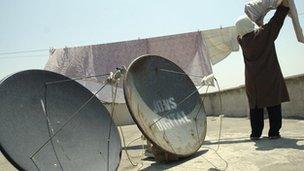 Iranian woman hanging washing next to satellite dishes