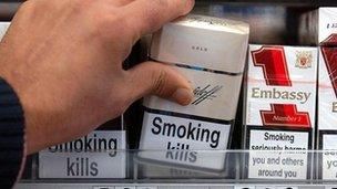 File photo dated 19/03/2007 of a shop assistant reaching for a packet of cigarettes on sale in an off licence