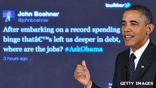 Barack Obama in front of a screen displaying a tweet