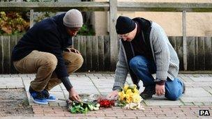 Two men lay flowers on the Stephen Lawrence Memorial in Eltham on 3 January 2011 after the jury's verdict