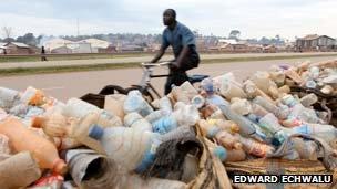 A man in Uganda rides past plastic bottles in Kampala (Photo: Edward Echwalu)