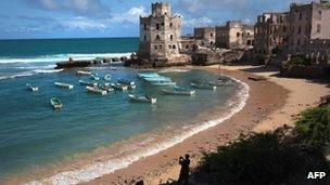 An African Union soldier taking a photo of a cove in Mogadishu in August 2011