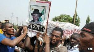"""Protesters carrying mock coffin of President Goodluck Jonathan reading """"Rest in Pains"""""""