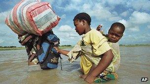 Mozambique: A woman holds on to her husband while trying to cross a floodplain, Friday 25 February 2000