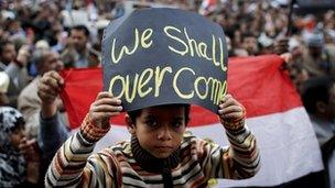 An Egyptian boy poses with a sign in front of anti-government protesters in Tahrir Square
