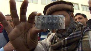 Man holds up packet of suspect pills
