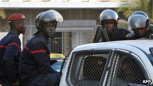 Riot policemen sit on the back of a pickup truck as they patrol the street in Dakar on 28 January 2012