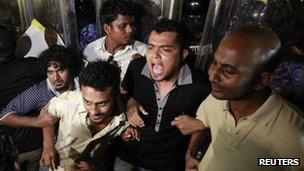 Supporters of former Maldives president Mohamed Nasheed shout slogans in front of police officers during a protest in Male on 12 February