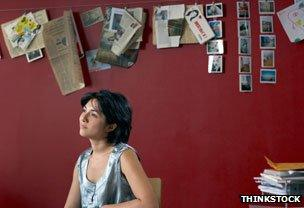 Woman in office, wall decorated with postcards and artworks and drawings
