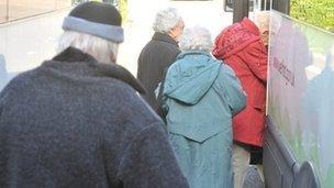 Elderly people getting on a minibus