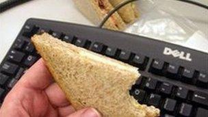 Worker eating sandwich at desk