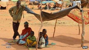 A woman and her children sit under a shelter at a Malian refugees camp in Chinegodar, western Niger (4 Feb 2012)