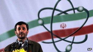 Mahmoud Ahmadinejad in front of an Iran nuclear symbol in Natanz