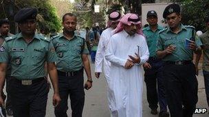 Bangladeshi policemen and Saudi officials inspect the area where a Saudi Arabian diplomat was shot dead in Dhaka